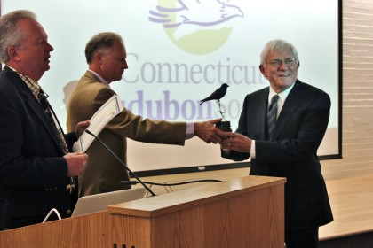 Connecticut Audubon President Alexander Brash, center, presents Phil Donahue with a Purple Martin carving, as Milan Bull, CAS senior director of science and conservation, looks on. Connecticut Audubon Society Photo by Claire Iwanowski.