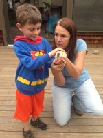 A young birder learns how to hold a bird.  Photo by Danielle Reinhart.