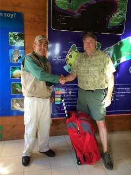 EcoTravel Director Andy Griswold, right, shakes hands with a representative of the Cuban national park as the presents a suitcase full of binoculars and field guides.